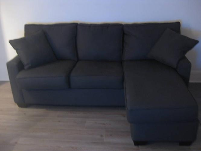 Charcoal couch with floating ottoman and 2 throw pillows