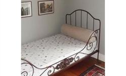 This authentic 19th century French iron campaign day bed has wonderful oxidization to the frame, sits on 4 wheels, and collapses to fold flat. It has beautiful scroll work with a decorative floral centre medallion. Frame photo without mattress is a
