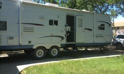 Trailer has one slide in dining and living room area. Bedroom has a queen size bed in front with wardrobe on either side and front bathroom, it also has jack and Jill bunks the bottom bunk is larger. Camper sleeps up to 8. kitchen has 3 burner stove with