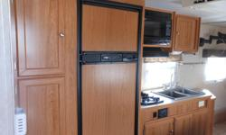 Front Queen Walk-around Bed. Rear Bathroom. Side Dinette. Large Fridge with Freezer. 2 Burner Stove. Microwave. VERY CLEAN