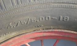 Two (2) antique model A ford tires and rims, original, not after market. One 4.75 / 5.00 - 19 Dominion Royal ( Peerless ) and one 4.75 / 5.00 - 19 Standard. Tires good for show only, rims very good condition.