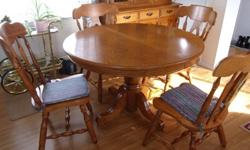 Round maple table with extra leaf, four chairs, buffet and hutch.