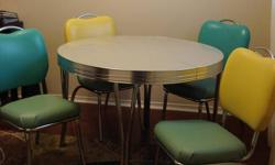 Round chrome table with extension piece to open up for seating 6.  Four chairs upholstered in a funky vinyl.