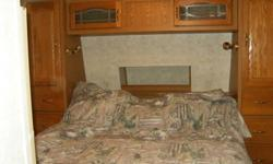 27 ft., solid wood cabinets, double slide, queen bed. Sleeps 4 Comes with awning, a/c, ladder and laundry chute.