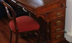 Antique Davenport desk in excellent condition, was refinished professionally. Desk is oak with Gothic influence, made around 1870-1890. Desk has a slant-top that opens for storage. The right side of the desk has four drawers and a long small secret
