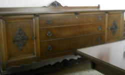 """Circa 1920 solid wood pedestal style dining room table, 6 chairs (one captains) matching buffet. Table is 60"""" x 48"""", with two additional 12"""" leaves which can be added. Matching buffet has cupboards at each end, each with interior shelf, and three drawers"""