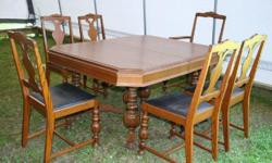 """This is a very old antique dining table and chairs that was refinished by a professional some years ago. It is solid oak and is in excellent condition, featuring a decorative """"Cannonball"""" base detail. - Dining Table has 2 leaves and measures 6""""2"""" x 3'11"""""""