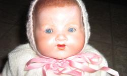 ANTIQUE GERMAN BABY DOLL, CRYING BOX, EYES OPEN AND CLOSE, SOME ORIGINAL CLOTHES, PORCELAIN HEAD AND HANDS, CLOTH BODY, COMES WITH WICKER CRADLE.   ON BACK OF NECK: A.M. GERMANY 351.14   ON ORIGINAL CRYING BOX: PATENTED 1917, MFD BY LLOYD MFG CO. WEST NEW