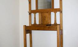 """Parting with oak hall tree from the Fergus area of Ontario. It measures 75""""x35""""x12"""". It has cast iron hooks in the shape of a snake, a lift up lid for gloves, etc. and a bevelled mirror complete with age spots. Its lightweight and tucks back nicely into"""