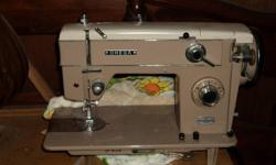 This sewing machine is about 50 yrs old and still works.  Comes with cabinet