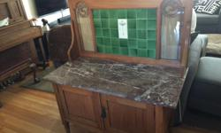 """This beautiful washstand was passed down to us, but we no longer have room for it. It has a thick granite top, lovely tile facade on the back and intricate carved detail. It is in great shape and sits on its original casters. 39"""" wide, 19"""" deep and the"""
