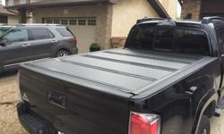 Bak Industries Fibermax Tonneau cover. It will fit a 2005-2015 Toyota Tacoma. Installation takes less than 20 minutes, and the cover only weights 30-40 pounds, easy to install alone. I've owned this cover about 3 years. The Fibermax has a fiberglass shell