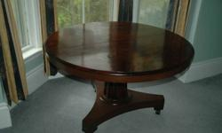 REDUCED PRICE 49 3/4ins diameter mahogany breakfast (tilt-top) table.  Plain tapered column support on a triangular base with 3 (new) casters. Two board top with matching grain showing slight separation.