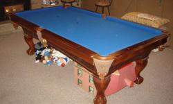 Beautiful solid Walnut 4' x 8' Beringer pool table. The table has blue felt, claw feet and a slate top. The table and felt are in mint condition. Included with the table is; 4 standard cues with rack, rake, short cue, 2 sets of balls, games and cover. If