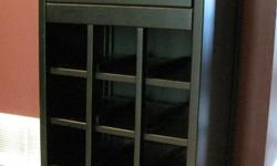 This black wine cabinet has a pull out drawer that glides open easily and has 4 shelves that will hold 12 bottles of wine. It's 35 1/2 inches tall so you can use the top as a shelf. It measures 18 3/4 x 16 inches. The drawer is 13 3/4 wide x 12 3/4, and 4