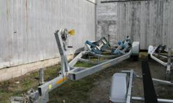 """Tandem axle galvanized trailer.   Surge brakes on both 6000lb axles. Versatile adjustable bunk set-up.  Spare tire and rim.  Suitable for up to 32 ft +/- boat.  Currently set up for 31' Larson Cabrio 310 2 5/16"""" coupler Heavy Duty, axles, and wheels,"""