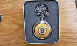 """Boston Bruins """"Pocket Watch"""" with Original Tin I have for sale a Boston Bruins """"Pocket Watch"""" with Original Tin and pocket chain. The watch measures 1 3/4"""" in diameter. The watch features a silver casing, with the Boson Bruins logo in gold, black and"""