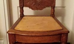 Lovely carved oak side chair. Antique, purchased in California. It looks like the seat was originally caned. It has the holes. The wood was on the seat when I purchased it. I used it covered with a piece of antique Persian carpet. Or, put a pot of flowers