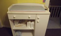 White change table with pad on top. Pad is blue on one side pink on the other. Has drawer and cupbaord for Storage. Also has 2 shelves for diapers and wipes. $25.00 obo