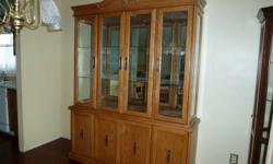 """Oak, 2 piece, beautiful condition.  Bottom hutch has 4 doors, upper cabinet has four glass doors, two glass shelves, mirror backing and interior light.  Dimensions:  64"""" wide, 85"""" total height, 17"""" deep."""