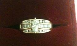 A beautiful Marquis shape center stone a row baguettes on either side then two rows of princess cuts underneath.   The center stone is .35 the rounds are .22 the baquettes are .20 the total weight of the ring is 5.6 grams   I had an appraisal done by