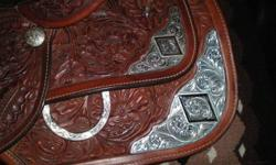 This saddle is in very good condition. I no longer need it because we Barrel Race now. It has the a hand carved pattern pattern on it, it also has cut outs under the fenders so you can get your legs rite on your horse. It has a 15 inch seat with Quarter