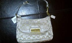 Beautiful, classic and elegant!!!   Brand new with the tags.   This purse if NOT an outlet style.   Khaki Signature sateen with cream trim.  Measures 10`` x 6` x 3`` deep.   Adjustable strap. GUARANTEED AUTHENTIC or twice your money back- this comes to