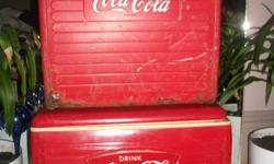 Two Coca-Cola Coolers. The top one (in the photo) is a 1955 beach cooler. Has some damage to the bottom of it; however, it does have a metal inside as shown in the pictures.. Made at the St.Thomas Tin Company in Canada. The bottom one is in excellent