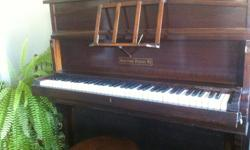 """This antique """"yachting piano"""" was designed to fit into small apartments--or elegant motor yachts. Its keyboard folds up vertically and clips into the piano itself for sleek storage and the music stand pops into the piano's hinged lid. 3 keys are omitted"""