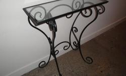 """Glass topped console with curly black metal legs. Top measures 27"""" x 11"""" and stands 31"""" high. Excellent condition. Pick-up only; downtown Toronto location."""
