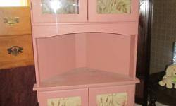 I have a paintable corner cabinet with glass doors on top, and solid doors on bottom, with a display shelf in the middle. The floral decor on the unit is easily removed, as it is just decorative unattached paper. email amanda at kincsem1015@hotmail.com if