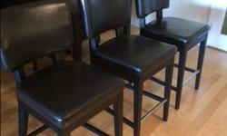 COUNTER STOOLS Three (3) Counter Stools. Seat height: 63.5 cm (25 in.). Easy to wipe clean, Faux Leather Finish (Brown, Expresso) seats and sturdy hardwood legs are finished in a dark espresso stain with a practical chrome footrest with the high back seat