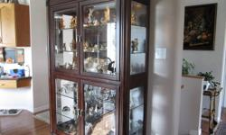 Solid wood curio cabinet with two glass shelves upper and 2 lower. Light at top of cabinet. Great for your preciouis ornaments or crystal. In good condition $300 OBO