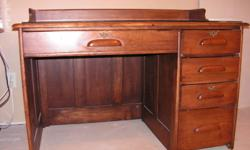 This desk is estimated to be about 60 -80 years old. I believe it is made from maple but am uncertain about this. It has plate glass covering the surface.