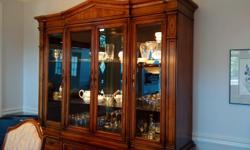 "Thomasville dining room table with pedestal legs, six chairs and hutch, all in excellent condition. Table measures 42"" wide and 76"" in length with two additional 18"" extensions. Buffet features glass shelves and interior lighting."
