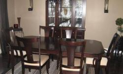 """Dark wood dining room set including table, 6 chairs, buffet & hutch. Table is 42"""" x 64 without leaf and 42 x 82"""" with leaf. Table has a few marks but overall good condition. Two end chairs have arms, fabric is beige pattern. Buffet is 56"""" wide x 34"""" high."""