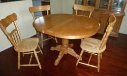 """Beautiful maple dining set - table and four chairs.  Table without leaf is almost circular 40"""".  With leaf 48"""" long, 40"""" wide.  Heavy centre pedestal.  Excellent condition."""