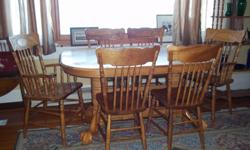 """Double pedestal oak dining table and six chairs and two large leafs,all sturdy and in very good condition. Size 59"""" plus 18"""" per leaf by 41""""."""