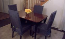 I have an elegant 5 piece dining table set. The table is hardwood with a red oak top and a black base.The chairs have a grey covered fabric that was just washed. The set is in great condition and the chairs very comfortable.. The dimensions of the table