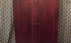 Selling my elegant large cabinet. Has a red mahogany finish. In MINT condition. Could be used as a regular storage armoire or as a TV cabinet. Has beautiful crown molding at the top wiith details on the doors and drawer. Has a pull out shelf. Has a large