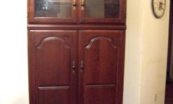 """Selling a very fancy large mahogany TV cabinet. In great condition. Very expensive piece. Has beautiful molding and detail with gold handles. The top has a glass shelf. The middle has a DVD shelf and the doors can be folded in. Space for a 40""""TV inside."""