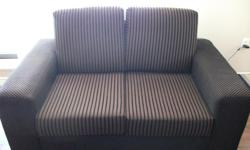 This love seat is brown with black stripes. It is in excellent condition and would make a great addition to your living room.