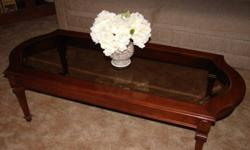 Dark wood framed, traditionally styled, sturdy coffee table with glass inlay.  Excellent condition.  Please email or call if interested.  Asking $40.00.