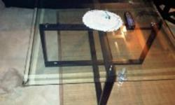 Glass tables both have blk iron stands great conditon no scratches one table is rectangle one is square modern shape   70 dollars each 289-668-4253