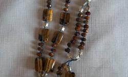 This is a beautiful piece and my personal favourite! The dark chocolate drop is cleverly accented with silver and butterscotch stones striated with black and dark brown. Honestly the photos do not do this lovely necklace justice ..  Sure to make a special