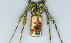 Inch long light wooden pendant with printed image of Anubis on real Egyptian papyrus with hieroglyphs on reverse. Glossed. Approx 25 inch long hand woven blue and yellow cord, continuous loop. Twisted strands on either side of pendant are slightly stiff