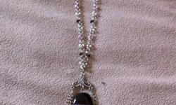 This necklace has a black and pink theme. The stone in the middle is semi precious agate. There are black, pink and clear beads linked into the chain. This ad was posted with the Kijiji Classifieds app.