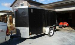 Excellent Condition V-Nosed 5' x10' cargo trailer. Purchased new 3 1/2 years ago. (Have reciepts)  Extra's include 4 recessed tie downs inside, 2 flow thru vents and interior lighting.  Has a single drop down door for easy access, ie( motorcycle,