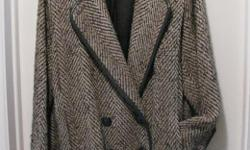 This herringbone wool jacket, designed like a blazer, is a size 9/10. It's double breasted, button on the folded cuff, faux black leather piping around the collar, and pleated shoulder folding down to the pocket. It's 87% wool, 23% rayon and 10% rayon.