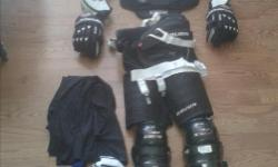 A complete set of Men's Hockey Gear. Generally size Large. In great shape. Clean. Includes helmet, shoulder pads, elbow pads, gloves, pants, knee pads. Also includes neck protector (still in pkg), garter belt, black practice jersey, blue socks. If items